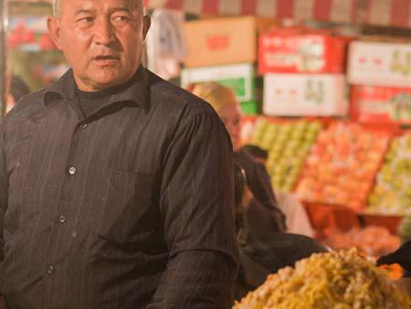Uighur man selling chickpeas and capsicum