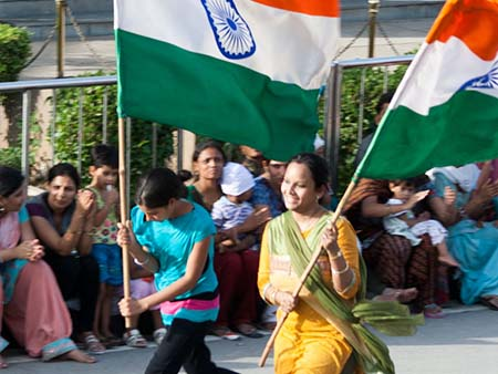 Two girls running with a large Indian flag