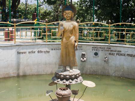 A standing Buddha statue at the base of the hill